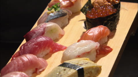 shot of various types of sushi on a wooden plate - raw food stock videos & royalty-free footage