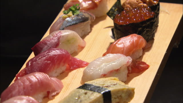 shot of various types of sushi on a wooden plate - sushi video stock e b–roll