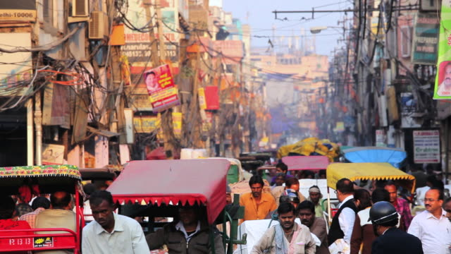 ms shot of vehicles and people at busy chandni chowk market / delhi, india - risciò video stock e b–roll