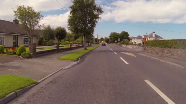 pov shot of vehicles on street amidst houses in town against sky during sunny day - galway, ireland - sunny video stock e b–roll