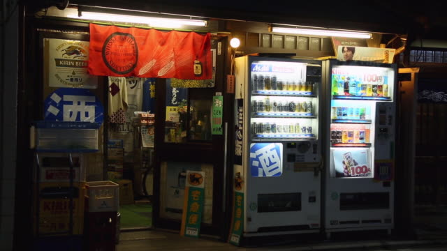 MS Shot of vending machines with lighting placed in front of liquor store at night with bicycles crossing at store front / Gionmachi, Kyoto, Japan