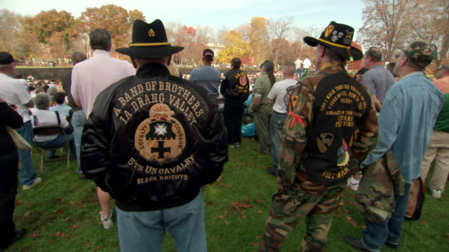MS Shot of Veterans wearing hats and camouflage clothes stand and listen during Veterans Day ceremony at Vietnam Veterans Memorial Wall / Washington, District of Columbia, United States