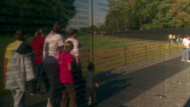 CU TS Shot of Vietnam Veterans Memorial Wall following reflection of family and other visitors as they walk along wall / Washington, District of Columbia, United States