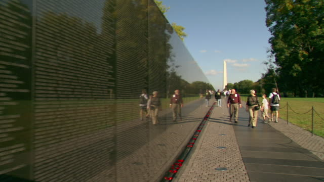 MS PAN POV Shot of Vietnam Veterans Memorial Wall starting with names in wall to path alongside it where visitors walking toward / Washington, District of Columbia, United States
