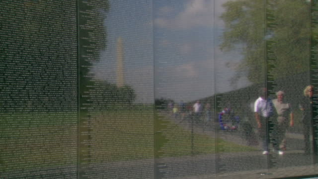 stockvideo's en b-roll-footage met cu zi shot of vietnam veterans memorial wall with reflection of visitors and washington monument / washington, district of columbia, united states - vietnam veterans memorial