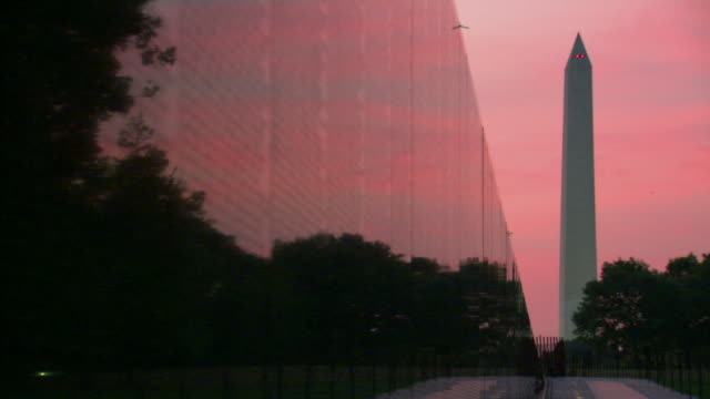 MS Shot of Vietnam Veterans Memorial wall with Washington Monument at sun rises / Washington, District of Columbia, United States