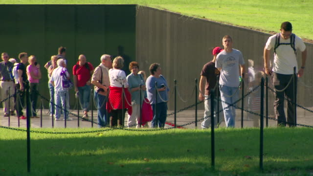 ms r/f shot of vietnam veterans memorial with visitors walking alongside wall / washington, district of columbia, united states - vietnam veterans memorial video stock e b–roll