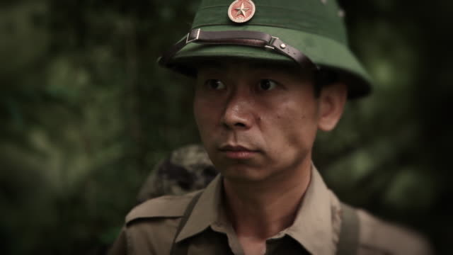 CU Shot of Vietnamese NVA soldier is observing jungle, behind him U.S. special operation forces soldier appears with combat knife / Jungle, Hue, Vietnam