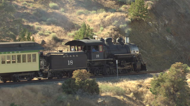 cu aerial zi ts shot of virginia and truckee railroad train running up hill and train rounds bend / nevada, united states - locomotive stock-videos und b-roll-filmmaterial