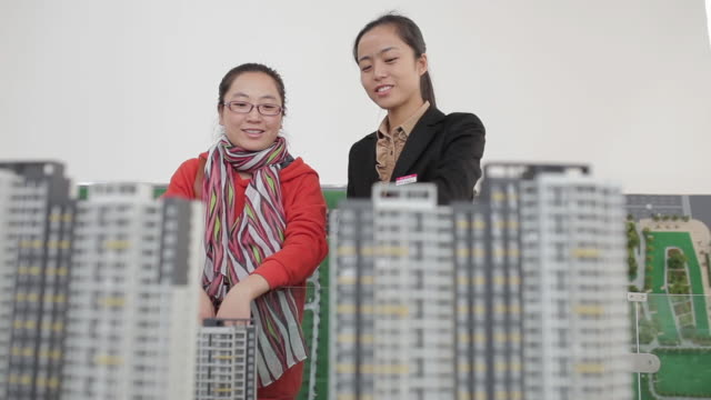 ma la pan shot of visitor and saleswoman talking about apartment models in real estate sales center / xi'an, shaanxi, china  - exhibition stock videos & royalty-free footage