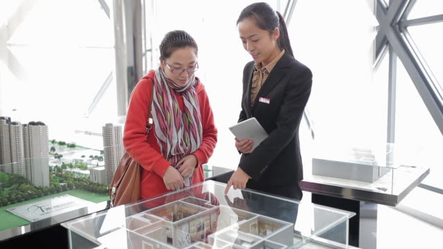 MS Shot of Visitor and saleswoman talking about apartment models in real estate sales center / Xi'an, shaanxi, China