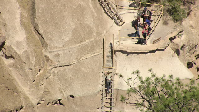 CU AERIAL TU TD Shot of visitors on ladders at mountain among cliff dwellings at Bandelier National Monument / New Mexico, United States