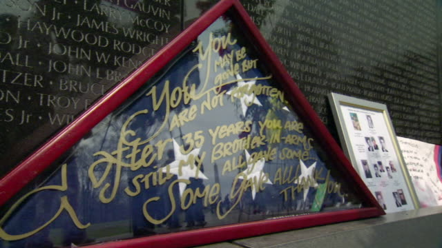 cu shot of visitors reflection in reads you may be gone but you are not forgotten frame at vietnam veterans memorial wall / washington, district of columbia, united states - ベトナム戦争戦没者慰霊碑点の映像素材/bロール