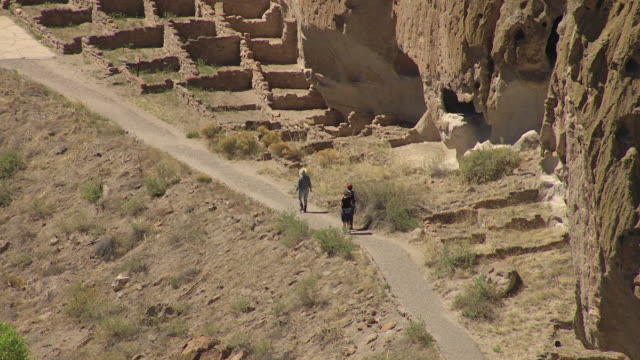ms aerial shot of visitors walking by ruins at bandelier national monument / new mexico, united states - pueblo built structure stock videos & royalty-free footage
