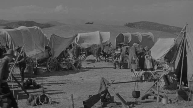 vídeos y material grabado en eventos de stock de ms shot of wagon train camp, horses, covered wagons and people - expansión hacia el oeste