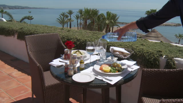 MS Shot of Waiter serving water / Tolox, Andalusia, Spain