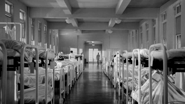 MS LS Shot of Ward in hospital with beds on both sides of room and Nurses and patients walking floor