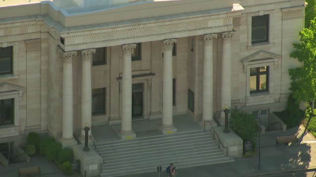 MS AERIAL Shot of Washoe County Courthouse entrance with people walking on foot path / Reno, Nevada, United States