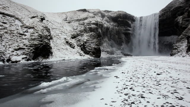 ms shot of water and icy snow coming down river at snowing condition / iceland  - waterfall stock videos & royalty-free footage
