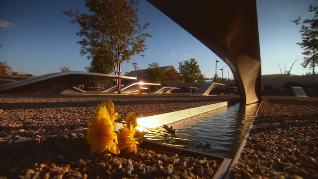 ms shot of water flowing with orange flowers under metal bench at outdoor september 11th memorial / arlington, virginia, united states - attentati terroristici dell'11 settembre 2001 video stock e b–roll