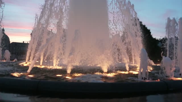 ms slo mo shot of water fountain in middle of street at sunset with pink hue with buildings / copenhagen, denmark - oresund region stock videos & royalty-free footage