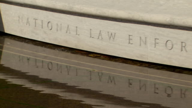 CU PAN Shot of water pool with National Law Enforcement Officers Memorial sign in stone / Washington, District of Columbia, United States