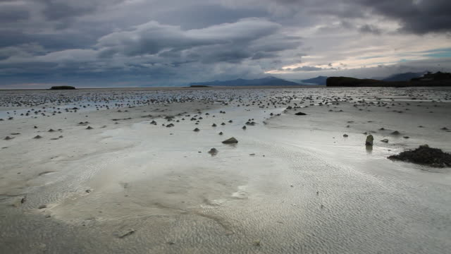 ws shot of water pools at low tide blow in strong gale force winds in front of ocean,  mountains and glaciers in distance / hofn, austur-skaftafellssysla, iceland    - low tide stock videos & royalty-free footage