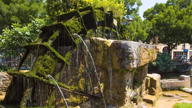 MS Shot of water wheel moving with covered by moss / L'Isle sur la Sorgue, France