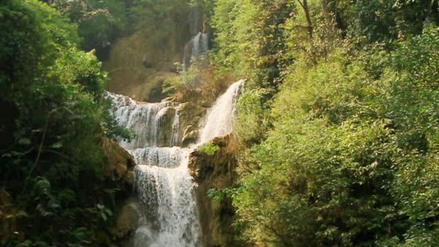 vidéos et rushes de ms slo mo shot of waterfall between green vegetation and brown rocks / kuang si, luang prabang, laos - waterfall