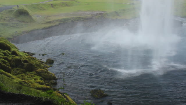 ms shot of waterfall crashing into body of water below with grassy rock face / vestmannaeyjar, sudhurland, iceland - wiese video stock e b–roll