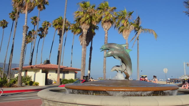 ms shot of waterfront and beaches and pier of beach for tourists on boardwalk with palms / santa barbara, california, united states - santa barbara bildbanksvideor och videomaterial från bakom kulisserna