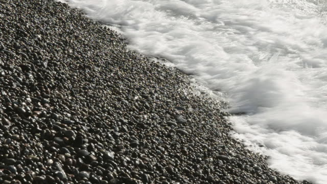 CU Shot of Waves at pebbles beach, UNESCO world heritage / Gulf of Porto, Corsica, France
