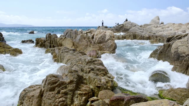 vidéos et rushes de ms shot of waves crashing against granit rock formation at beach and people fishing / propriano, corsica, france - granit