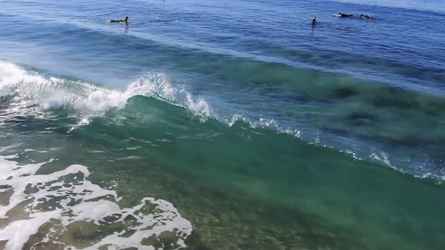 vídeos de stock, filmes e b-roll de cu aerial pov slo mo shot of waves crashing on beach with people swimming / laguna beach, california, united states - laguna