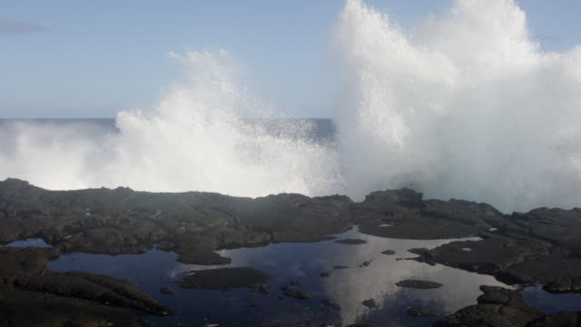 MS SLO MO PAN Shot of waves hitting on big rocks, boulders with big splash / Waipio, Hawaii, United States