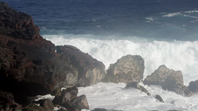 MS SLO MO PAN Shot of waves hitting on rocks near shore with big splash / Waipio, Hawaii, United States