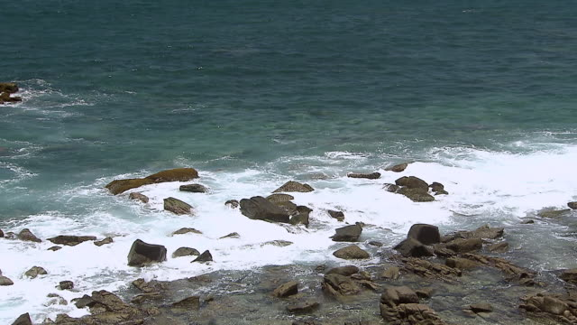 MS Shot of waves lapping at rocks to small beach next to Medano Beach / Cabo San Lucas, Baja California Sur, Mexico