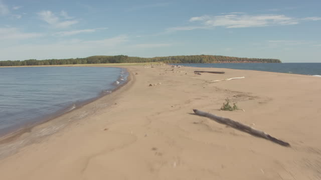 ms tu aerial shot of waves of lake superior and pull up for a low reveal of southern shore of apostle islands of outer islands / wisconsin, united states  - lago superiore video stock e b–roll