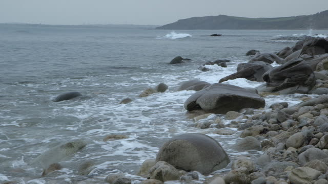 Shot of waves rolling onto a pebble beach on the coast of Dorset.