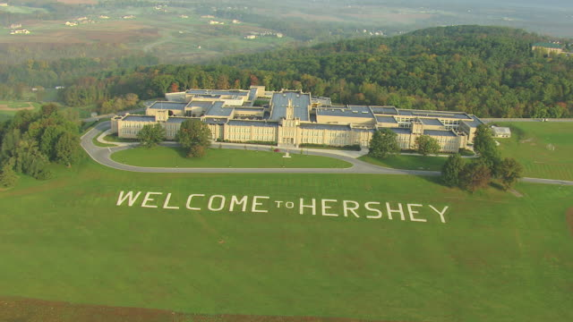 ws aerial td shot of welcome to hershey sign in grass in front of mansion building / hershey, pennsylvania, united states - pennsylvania stock videos & royalty-free footage