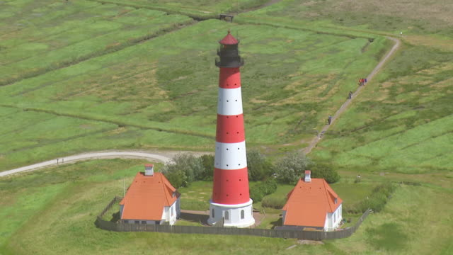 ws aerial ds zi zo shot of westerhever leuchtturm / sankt pete ording, schleswig holstein - schleswig holstein stock videos & royalty-free footage
