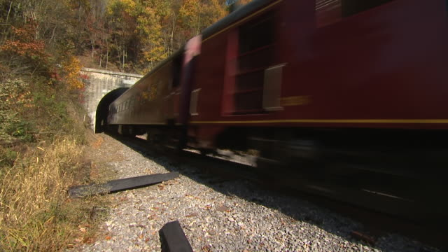 MS Shot of Western Maryland steam train on tracks rounding bend and driving through tunnel through mountain / Maryland, United States