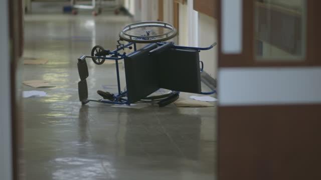 vidéos et rushes de ms tu shot of wheel chair and int old hospital hallway / leeds, west yorkshire, united kingdom - chaise roulante