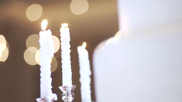 vídeos y material grabado en eventos de stock de 2 disparos de velas blancas con candelabro retro en el interior contra el fondo de la torta de bodas blanca borrosa. - haz de luz