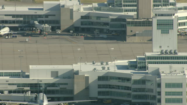 stockvideo's en b-roll-footage met ms tu aerial shot of white tent structures with peaks and airplanes on runway with air traffic control tower at denver international airport / denver, colorado, united states - dia