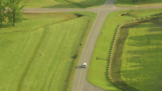 MS AERIAL TS Shot of white van on road through countryside with trees in Choctaw County / Mississippi, United States