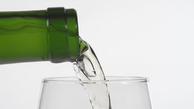 cu slo mo shot of white wine being pour into glass against white background / calvados, normandy, france - wine glass stock videos and b-roll footage