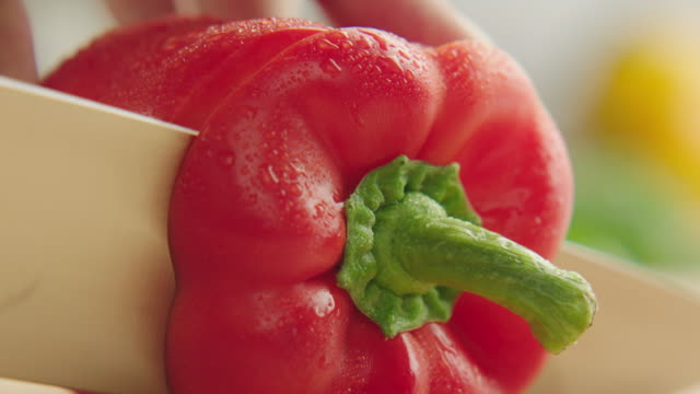 ecu shot of whole organic red bell pepper on kitchen cutting board and the stem top is sliced off with steel knife / los angeles, california united states - chopped stock videos and b-roll footage