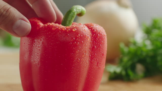 cu shot of whole organic red bell pepper on kitchen cutting board, the vegetable is held upright and cut in half with steel knife / los angeles, california united states - bell pepper stock videos & royalty-free footage
