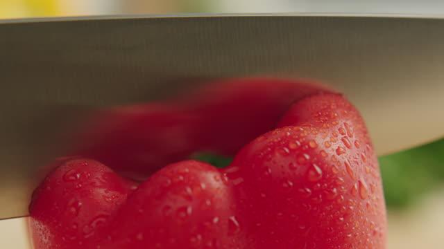 vídeos y material grabado en eventos de stock de ecu shot of whole organic red bell pepper, the vegetable is cut in two pieces with steel knife / los angeles, california united states - pimientos